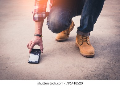the abstract image of the man picking a broken smartphone up from sement floor. the concept of broken, accident, daily life, mobile phone, electronic, repairing, warranty and technology.
