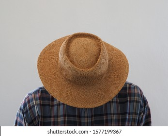 Abstract image. A man in a straw hat bowed his head to not see his face.
