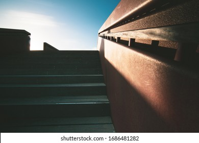 Abstract image of a modern designed strap in the dunes with a steel rusty railing illuminated with sunlight and a contrasting shadow
