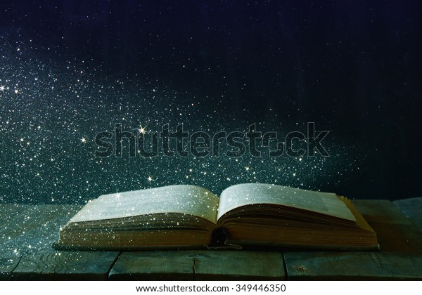 abstract image of open antique book on wooden table. selective focus. retro filtered and toned with glitter overlay