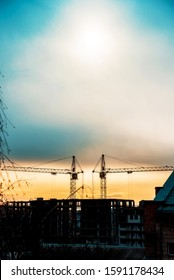 Abstract image of a pair of construction cranes on a sunrise background (progress, lower mortgage rates, falling house prices - concept)