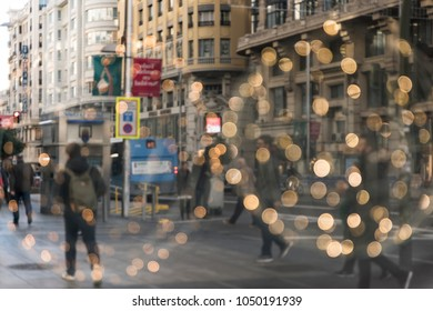 Abstract image of people walking along the Gran Vía of Madrid on a Christmas morning.