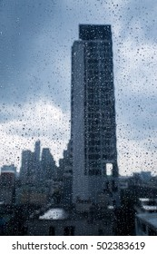 Abstract image of Rain drops on the dirty glass windows with modern office building background