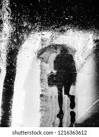 Abstract image of rain in New York City. Reflections from wet tile slabs. Pedestrians hurry on their business. Motion blur image