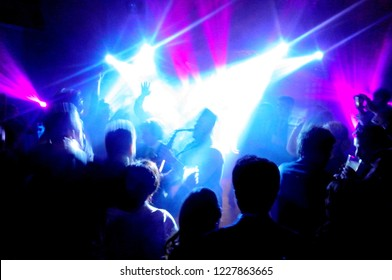 Abstract image of the silhouette of a saxophonist surrounded by a lot of people under the spotlights and neon lights in a pub or disco