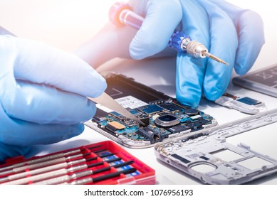 The abstract image of the technician assembling inside of smartphone by screwdriver in the lab. the concept of computer hardware, mobile phone, electronic, repairing, upgrade and technology.
