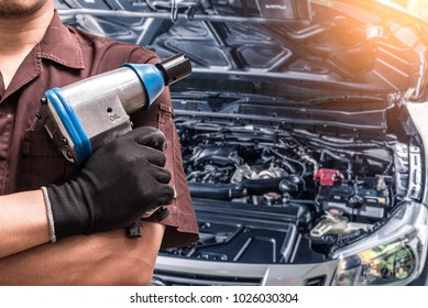 The abstract image of the technician hold the air wrench and blurred engine is backdrop. the concept of automotive, repairing, mechanical, vehicle and technology.