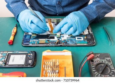 The abstract image of the technician repairing inside of tablet by screwdriver in the lab. the concept of computer hardware, mobile phone, electronic, repairing, upgrade and technology.