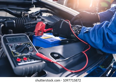 The abstract image of the technician using voltage meter for voltage measurement a car's battery. the concept of automotive, repairing, mechanical, vehicle and technology.