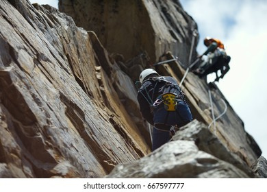 Abstract image of a two person rope of climbers on a rock tower.
