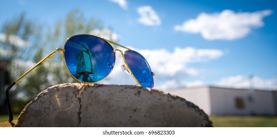 Abstract image using soft focus on aviator styled sunglasses with a old wood windmill reflection in the mirror like lens on a sunny blue sky day