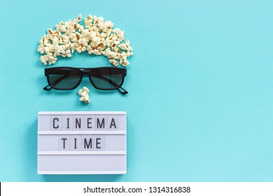 Abstract image of viewer, 3D glasses, popcorn and light box text Cinema time on blue paper background. Concept cinema movie and entertainment Flat lay Top view Copy space for text or your design.