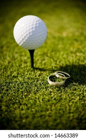 An abstract image of wedding rings lying next to a golf ball on a tee