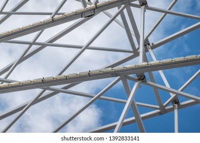 Abstract image of white steel struts and supports in front of a white-blue sky, abstract