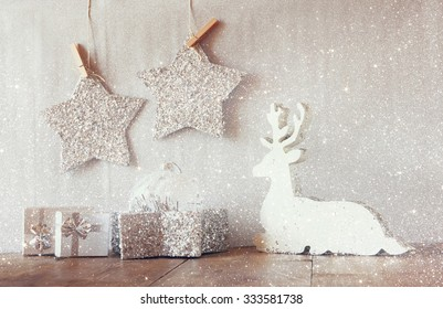 abstract image of white wooden reindeer and stars hanging on rope over glitter silver background