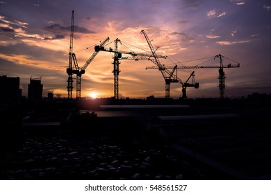 Abstract Industrial background with construction cranes silhouettes over amazing sunset sky