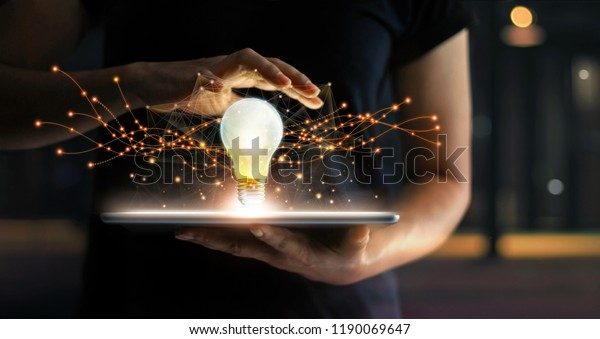 Abstract. Innovation. Hands holding tablet with light bulb future technologies and network connection on virtual interface background, innovative technology in science and communication concept