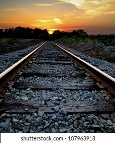 Abstract journey concept of a railroad heading into a sunset.