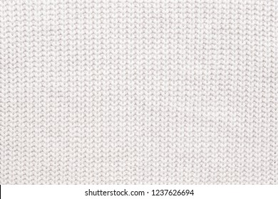 Abstract knitted background. White woolen sweater texture. Close up picture of  knitted pattern.