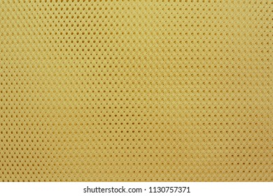 abstract knitted texture of fabric with a mesh pattern for a background or for wallpaper of yellow color