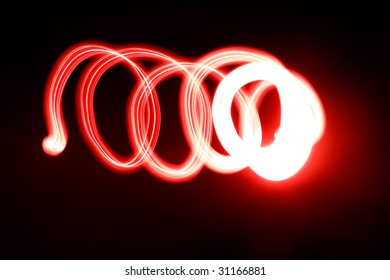 An abstract light background showing motion blurred light on a dark background.