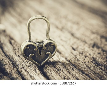 Abstract of love or Valentines Day concept.The golden heart love lock on old wooden  with blur background. Background for copy space text or quote. Vintage effect. and filtered process.