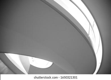 Abstrakter Low-Winkel, Nahaufnahme von moderner Architektur und Innenarchitektur mit kurvenreicher Decke und Glasbalustrade. Minimaler Innenhintergrund mit Spiralstruktur. Geometrische Schwarz-Weiß-Zusammensetzung
