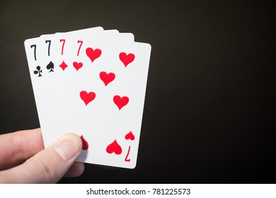 Abstract: man hand holding playing card four seven isolated on black background with copyspace