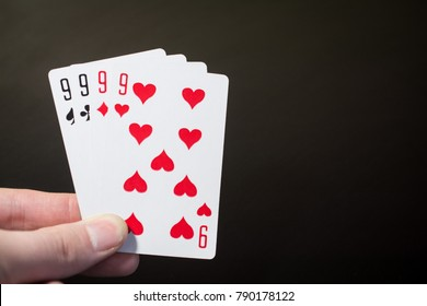 Abstract: man hand holding playing card four nine isolated on black background with copyspace poker set four nine