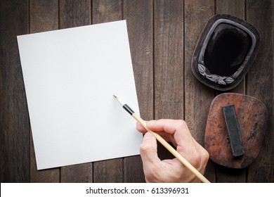 Abstract man hand white paper with bamboo calligraphy brush and inkstone on old wooden table. picture for add text or greeting card chinese new year. Chinese traditional painting text paper.