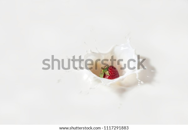 Abstract milk heart with falling berry. Milk splash with a drop and strawberry. Top view.