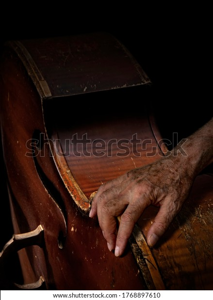 Abstract minimalist conceptual scene with old musician's hand on vintage scratched contrabass against black background. Serious music, sadness and loneliness concept