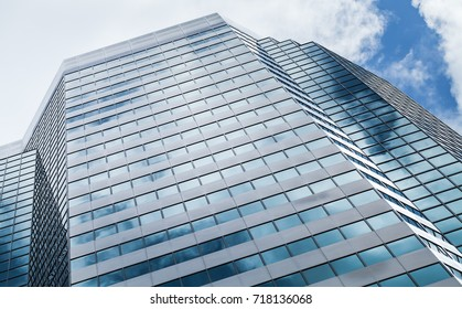 Abstract modern architecture background photo, office tower made of glass and steel with reflections of cloudy sky
