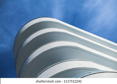 Abstract modern architecture fragment, round white concrete facade under blue cloudy sky
