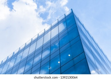 Abstract modern commercial architecture fragment, corner of walls made of shiny glass and steel under blue cloudy sky