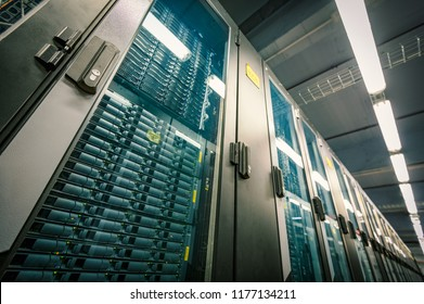 Abstract of modern high tech internet data center room with rows of racks with network and server hardware.