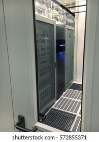 Abstract of modern high tech internet data center room with rows of racks with network and server hardware. View through the window of the door
