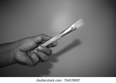 Abstract monochrome color of man hand holding the wooden paint brush isolated