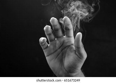 Abstract monochrome image of a hand and smoke