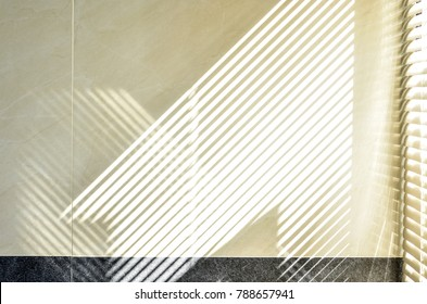 Abstract of morning light and shadow on tiled wall through window blind shutter. Parallel lines of light and reflection provide interesting abstract interior character. Light through blinds window.