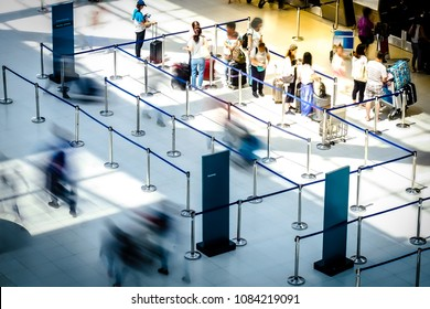 Abstract motion blurred image of people at the airport walking in line to their check in or departure gate
