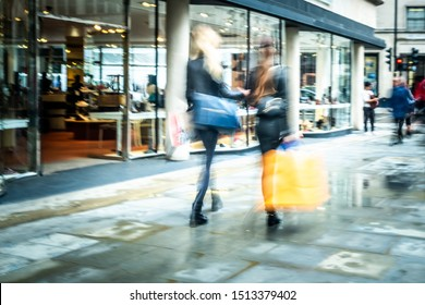 Abstract motion blurred shoppers with large shopping bags