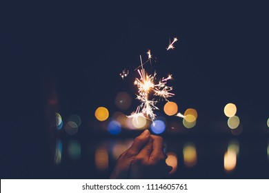 Abstract Motion Blurred Sparklers in woman hand holding at night city with line bokeh reflect on river side, vintage film grain style.sparklers for celebration christmas,festival party background.