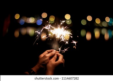 Abstract Motion Blurred Sparklers in woman hand holding at night city with line light bokeh reflect on river side, vivid film grain style.sparklers for celebration christmas,festival party background.