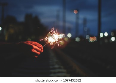 Abstract Motion blurred Sparkles by wind in blur woman holding hand  for celebration background with bokeh and railway to rail station(train station) on twilight blue sky background,Vintage Film Grain