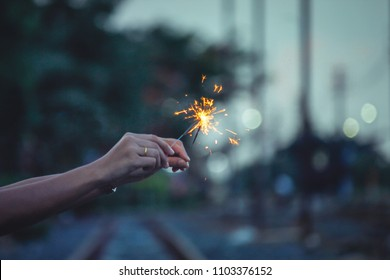 Abstract Motion blurred Sparkles by wind in blur woman holding hand  for celebration background with bokeh and railway to rail station(train station) on Low Light evening background,Vintage Film Grain