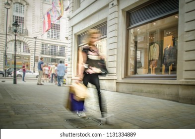 Abstract motion blurred view of female shopper on upmarket London shopping street