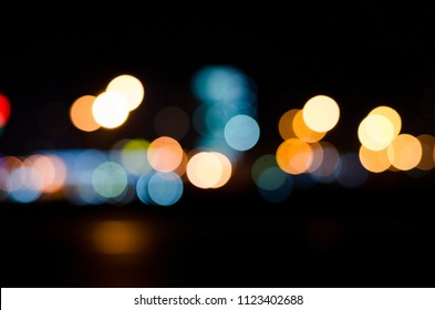 Abstract multicolored blurred and bokeh reflection of illumination from the headlights and illuminations on the road. Night life of the city