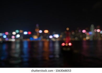Abstract multi-colored defocused lights Kong Kong commercial skyline across Victoria Harbor from Kowloon brightly illuminated and colored.