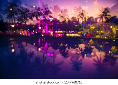 Abstract multiple-exposure defocused view at dusk of palm trees and neon lights of Ocean Drive reflecting in puddle at dusk in South Beach, Miami, Florida, USA